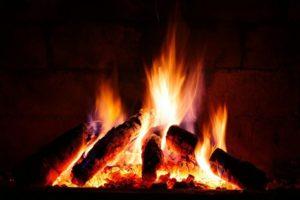caminetto acceso con fuoco e ciocchi di legno