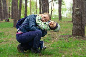 una mamma abbraccia il suo bambino in un bosco