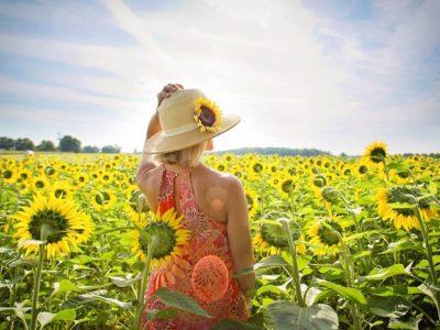 Mädchen, das über ihrer Schulter auf einem Gebiet von Sonnenblumen schaut. Entdecken Sie die Sommerangebote des Agriturismo La Porcareccia in der Toskana.