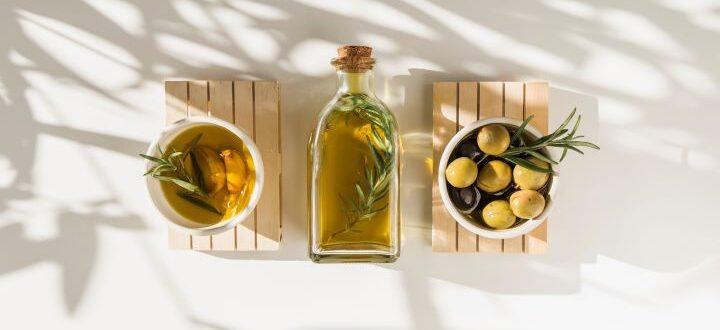 bottiglia di olio e ciotoline con olio e aromi su fondo bianco
