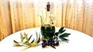 bottiglia di olio su un tavolo con rami d'olivo e olive nere